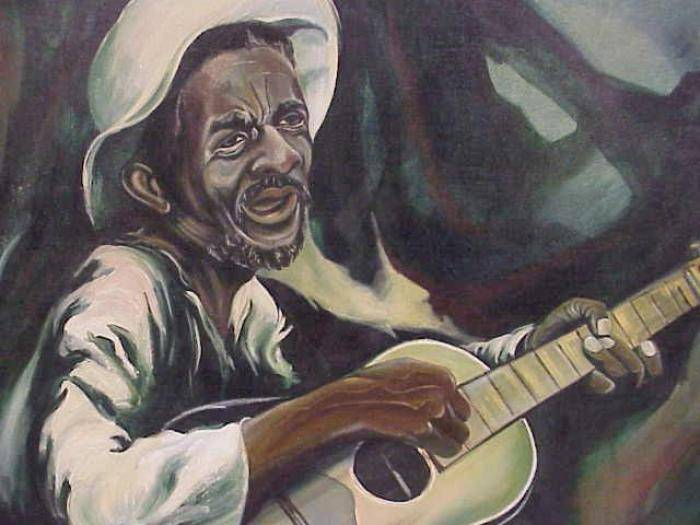 An older Black man in a white shirt and white hat hold a guitar and sings.